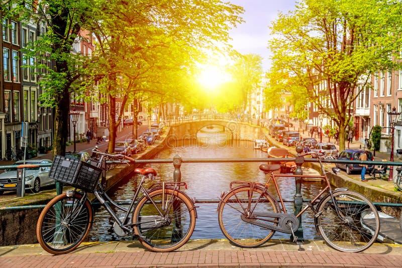 Gammal cykel p? bron i Amsterdam, Nederl?nderna mot en kanal under solig dag f?r sommar r royaltyfri foto