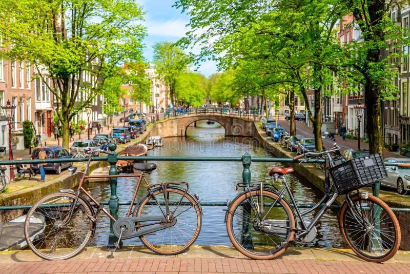 Gammal cykel p? bron i Amsterdam, Nederl?nderna mot en kanal under solig dag f?r sommar r fotografering för bildbyråer