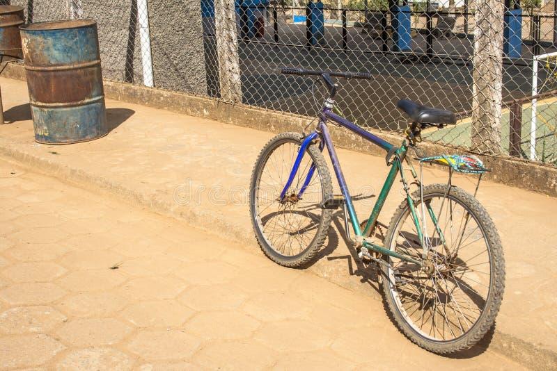 Gammal cykel som parkeras på en gata royaltyfri foto