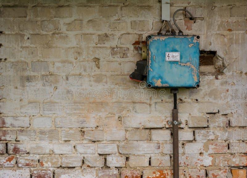 Gammal dålig rostig strömbrytareask på den red ut väggen royaltyfri foto