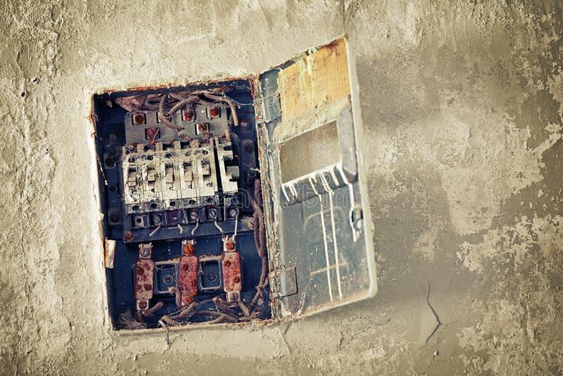 Gammal dålig rostig strömbrytareask på väggen fotografering för bildbyråer