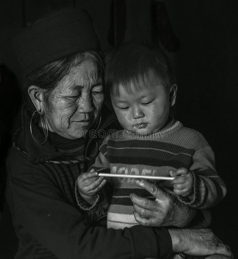 Gammal dam för Hmong stam som rymmer hennes sonson i hennes armar inom hennes hus, Sapa Vietnam royaltyfria bilder