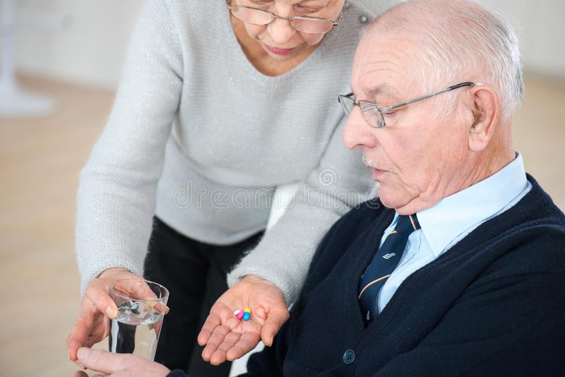 Gammal dam som ger preventivpillerar till den sjuka maken royaltyfria foton