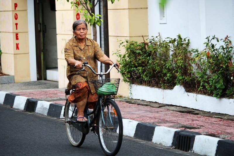 Gammal dam som kör bycicle royaltyfria foton
