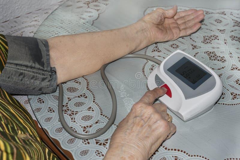 Gammal dam som kontrollerar hennes blodtryck fotografering för bildbyråer