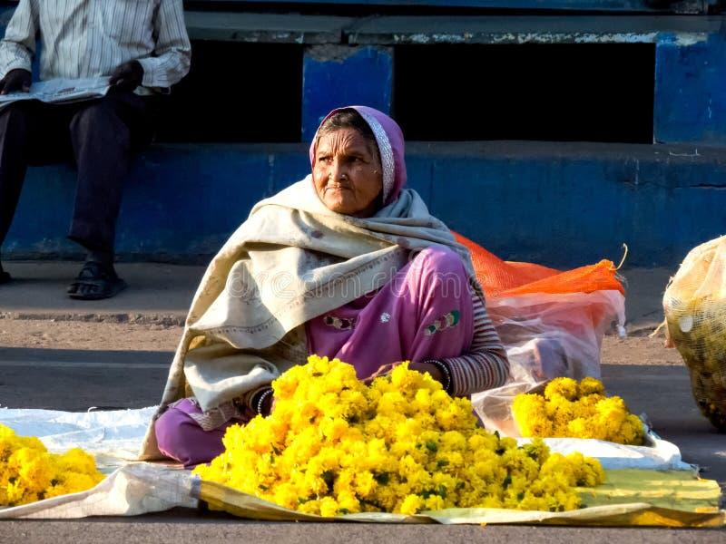 Gammal dam som säljer blommor på gatan arkivbild