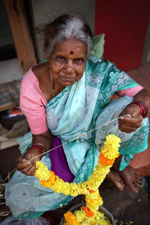 Gammal dam som säljer girlanden av blommor. Goa Indien. royaltyfri fotografi