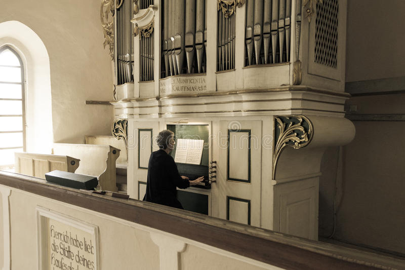 Gammal dam som spelar det medeltida kyrkliga organet arkivfoton