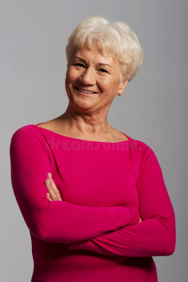 Gammal dams stående i rosa tillfällig kläder. royaltyfri fotografi
