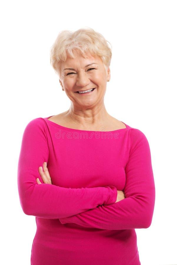 Gammal dams stående i rosa tillfällig kläder. royaltyfri foto