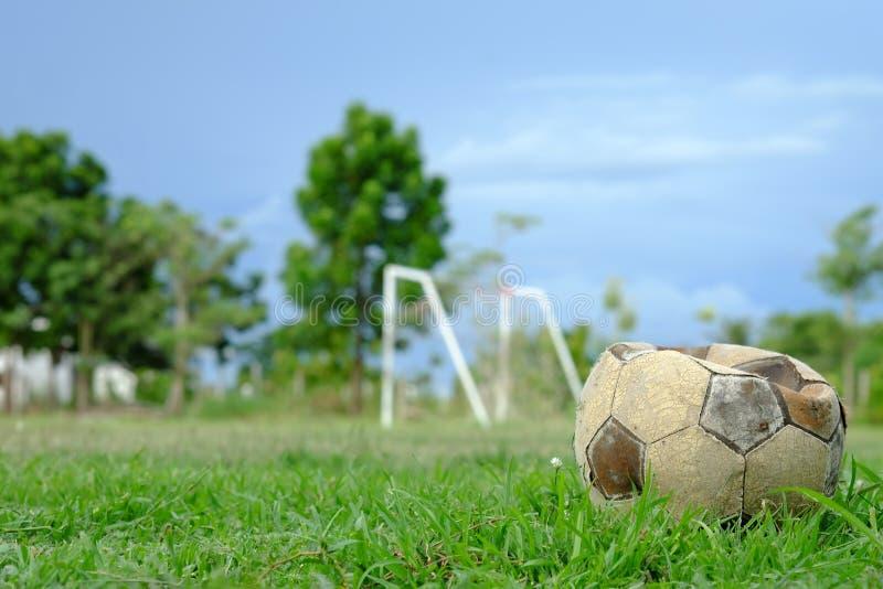 Gammal deflaterad fotbollboll, gammal deflaterad fotboll på det gröna gräset arkivbild