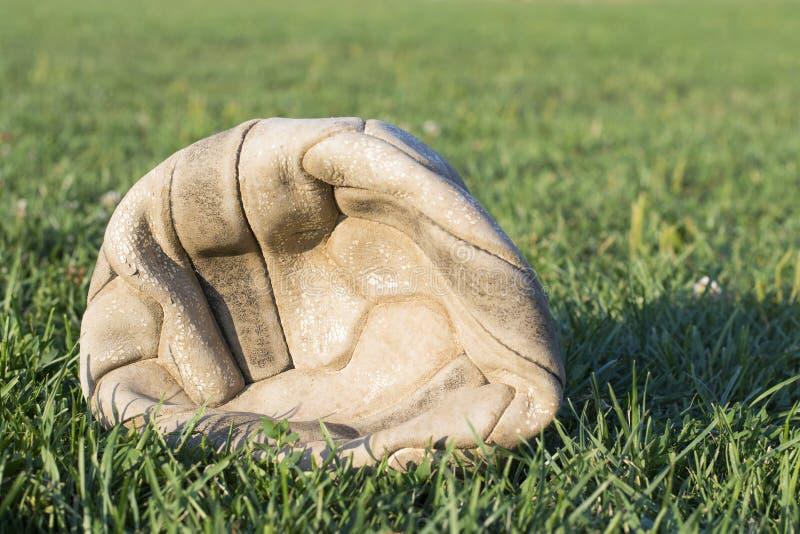 Gammal deflaterad fotbollboll på gräset för fotbollfält fotografering för bildbyråer