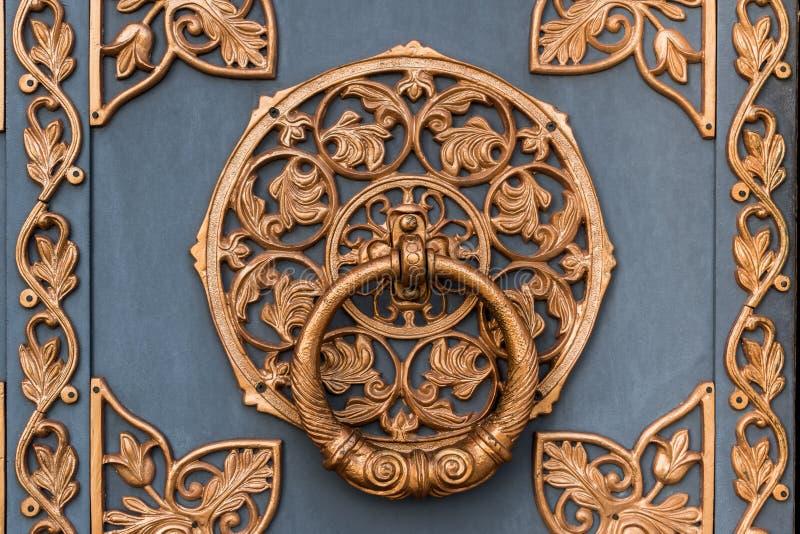 Gammal dekorerade svartmetalldörren med bronsprydnaden arkivbild