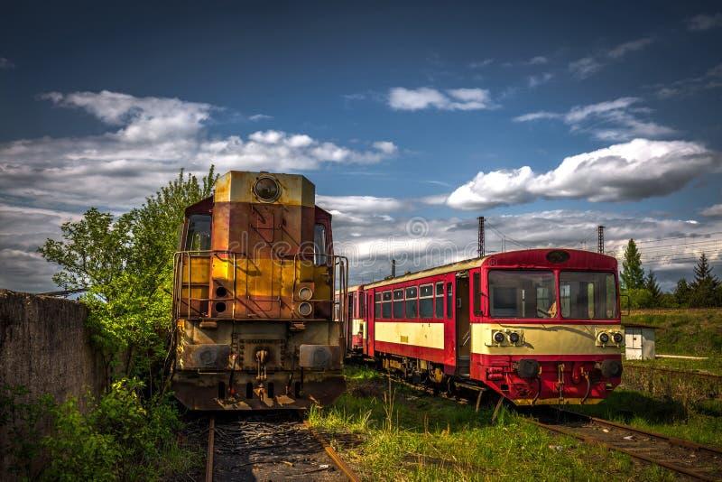Gammal diesel- lokomotiv i drevkyrkogård i sommaren med grönt gräs och träd i bakgrunden och den stora molniga himlen royaltyfria bilder