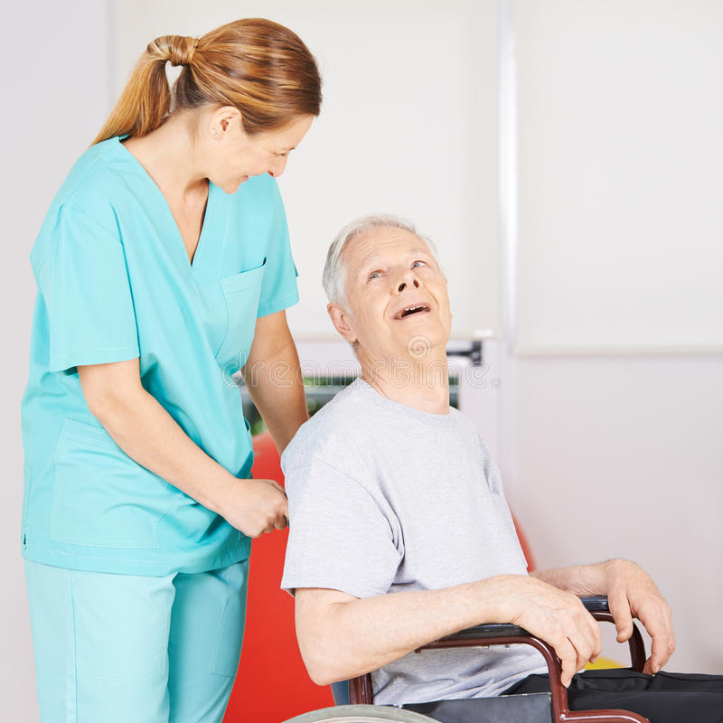 Gammal disbabled man i rullstol med den geratric sjuksköterskan royaltyfri bild