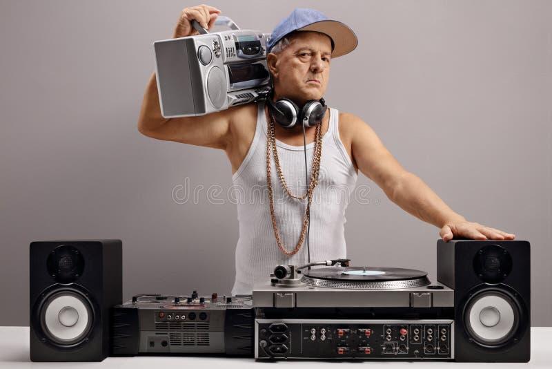 Gammal discjockey med en boombox- och musikalutrustning royaltyfri bild
