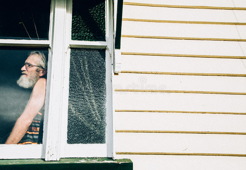 Gammal eftertänksam man som bara står i fönster av huset arkivbilder