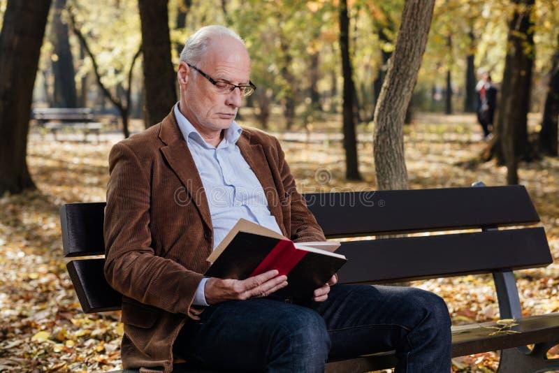 Gammal elegant man som utanför läser en bok arkivfoto
