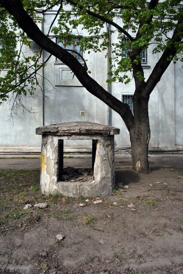 Gammal en förstörd ventilationsbyggnad, handikappade personer gjorde av betong, nära acerträd och den gamla gråa husväggen arkivbild