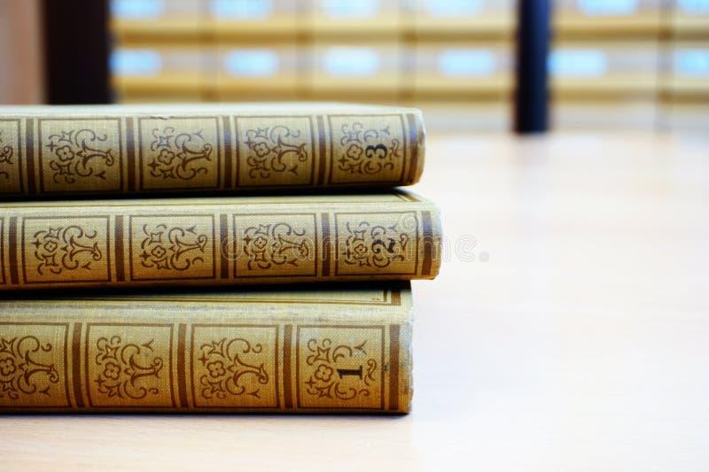 Gammal encyklopedi i tre delar på skrivbordet i arkivet fotografering för bildbyråer