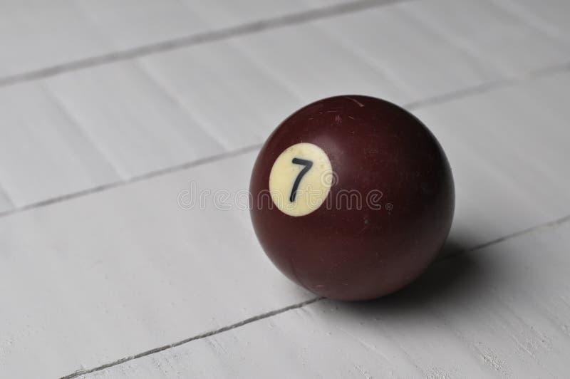 Gammal färg för brunt för nummer 7 för billiardboll på vit trätabellbakgrund, kopieringsutrymme fotografering för bildbyråer