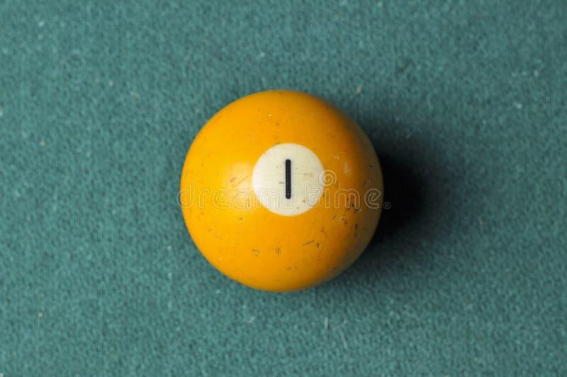 Gammal färg för guling för nummer 1 för billiardboll på den gröna billiardtabellen, kopieringsutrymme royaltyfri bild
