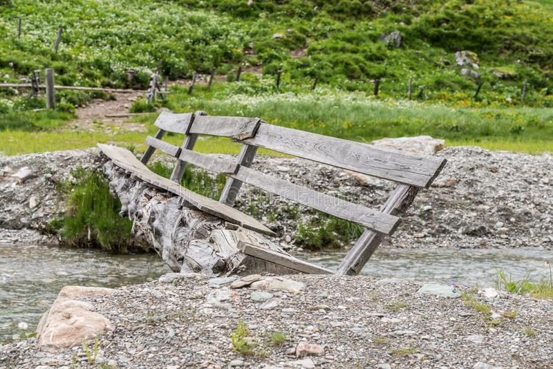 Gammal förfallen träbro över en bergström, Österrike fotografering för bildbyråer