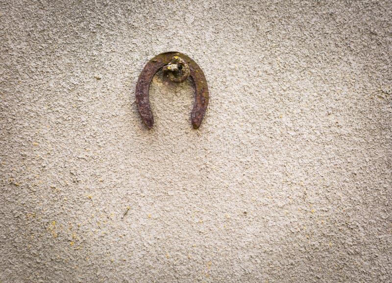 Gammal förstörd betongvägg med hängande horshoebakgrund royaltyfri foto