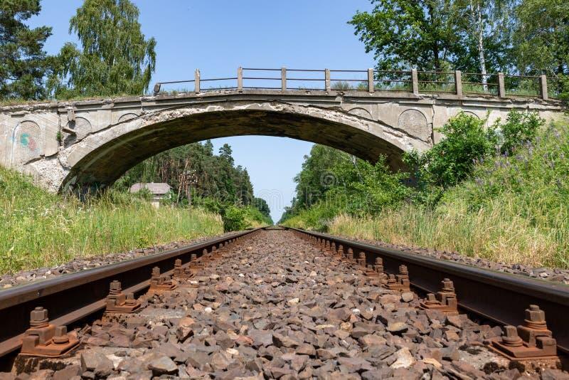 Gammal förstörd konkret planskild korsning över den järnväg linjen Gammal järnväg linje med en telegraflinje royaltyfri foto