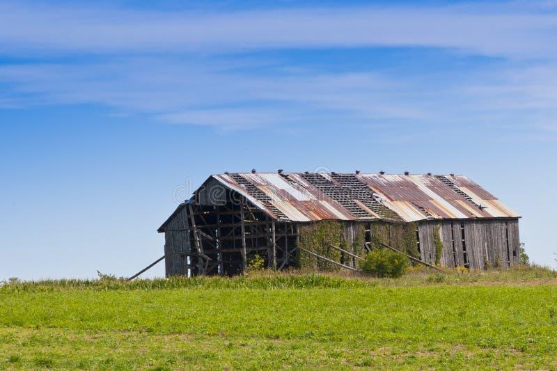 Gammal förstörd ladugård i lantligt land arkivfoto