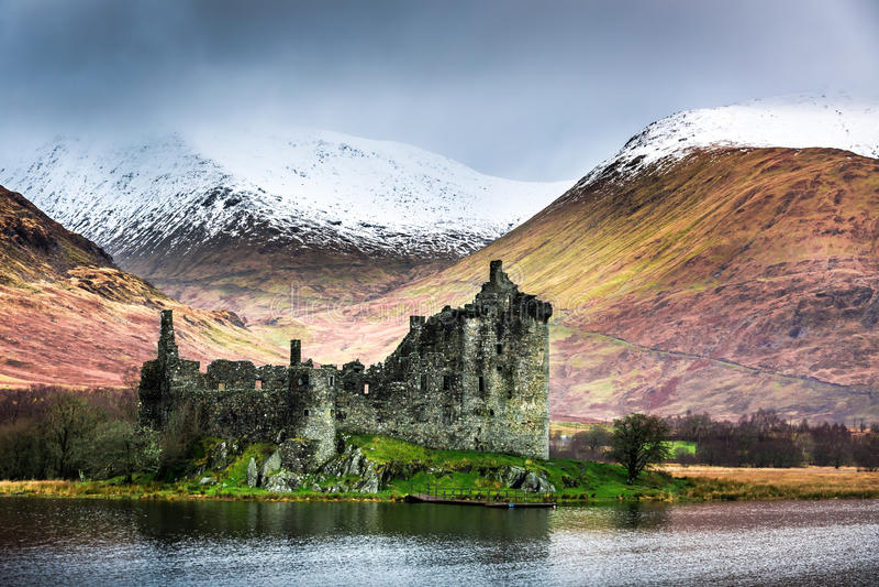 Gammal förstörd slott på bakgrunden av snöig berg