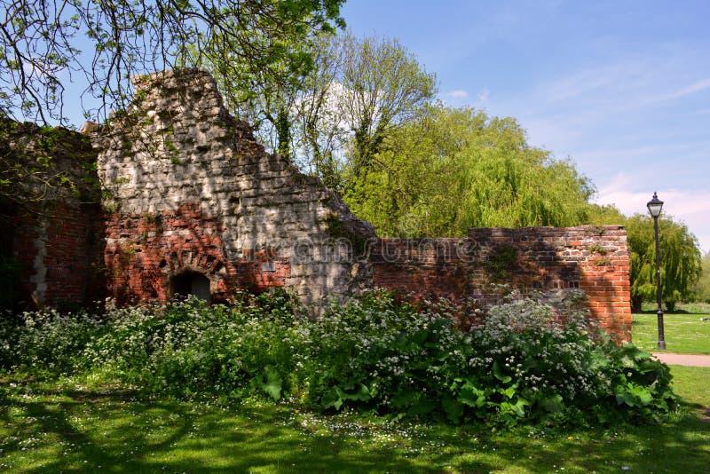 Gammal förstörd vägg från den röda tegelstenen i parkera i sommar, Waltham abbotskloster, UK royaltyfria bilder