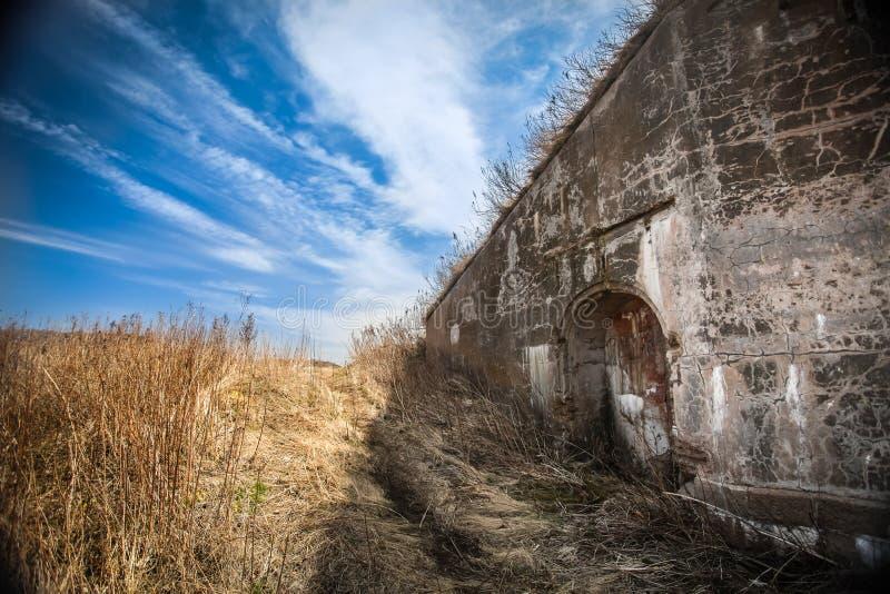 Gammal förstörd vägg med att fördjupa i fältet av torkat gräs och blå himmel med moln arkivbild
