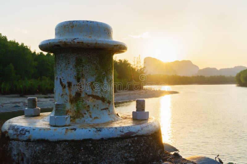 Gammal förtöja pollare i port på solljusmorgonen royaltyfria bilder