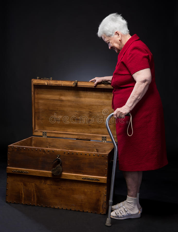 Gammal förvånad kvinna som ser in i en stor ask royaltyfria foton