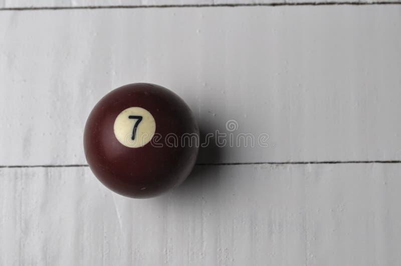 Gammal f?rg f?r brunt f?r nummer 7 f?r billiardboll p? vit tr?tabellbakgrund, kopieringsutrymme arkivbilder