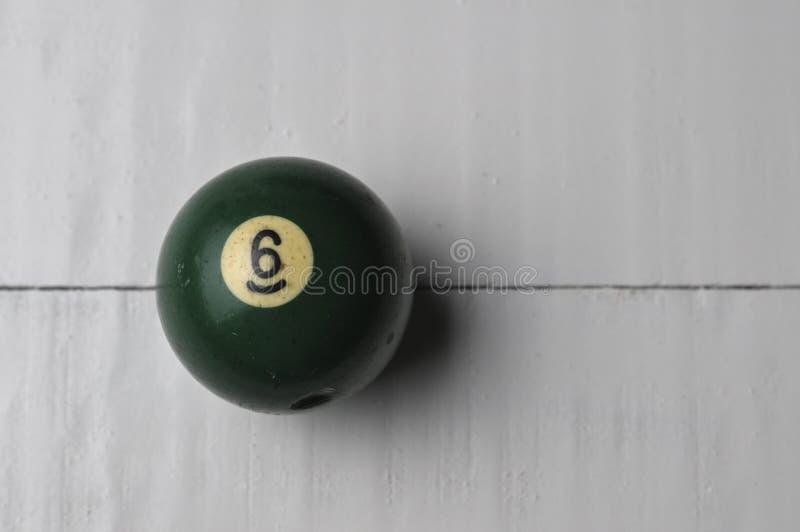 Gammal f?rg f?r gr?splan f?r nummer 6 f?r billiardboll p? vit tr?tabellbakgrund, kopieringsutrymme royaltyfria bilder