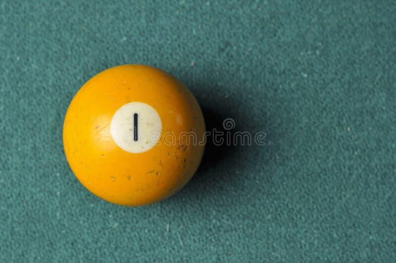 Gammal f?rg f?r guling f?r nummer 1 f?r billiardboll p? den gr?na billiardtabellen, kopieringsutrymme fotografering för bildbyråer