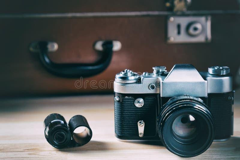 Gammal filmkamera med filmen mot bakgrunden av en tappningbruntresväska arkivfoto
