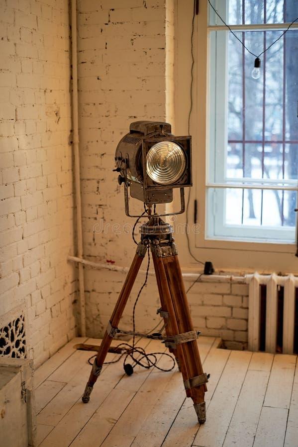 Gammal filmprojektor med en lins och en varm lampa På en tripod royaltyfria bilder