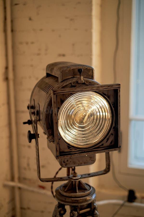 Gammal filmprojektor med en lins och en varm lampa På en tripod fotografering för bildbyråer