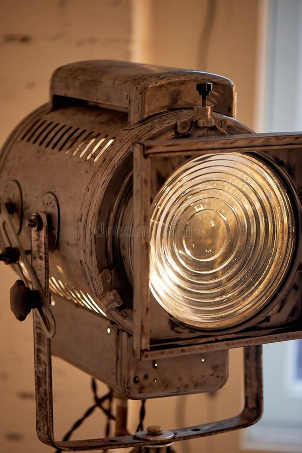Gammal filmprojektor med en lins och en varm lampa På en tripod arkivfoto