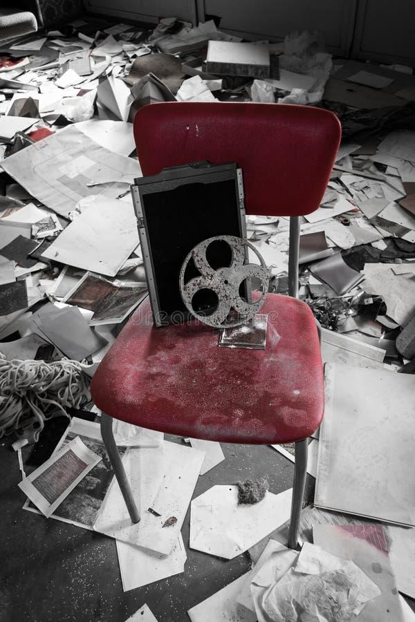 Gammal filmrulle för en projektor på en röd stol royaltyfri bild
