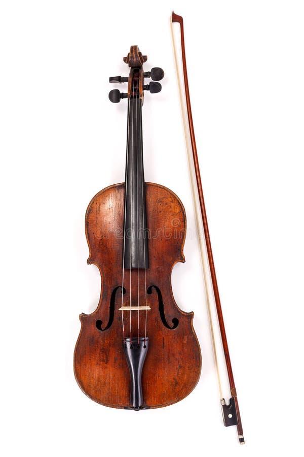 Gammal fiol med pilbågen på vit bakgrund arkivbild