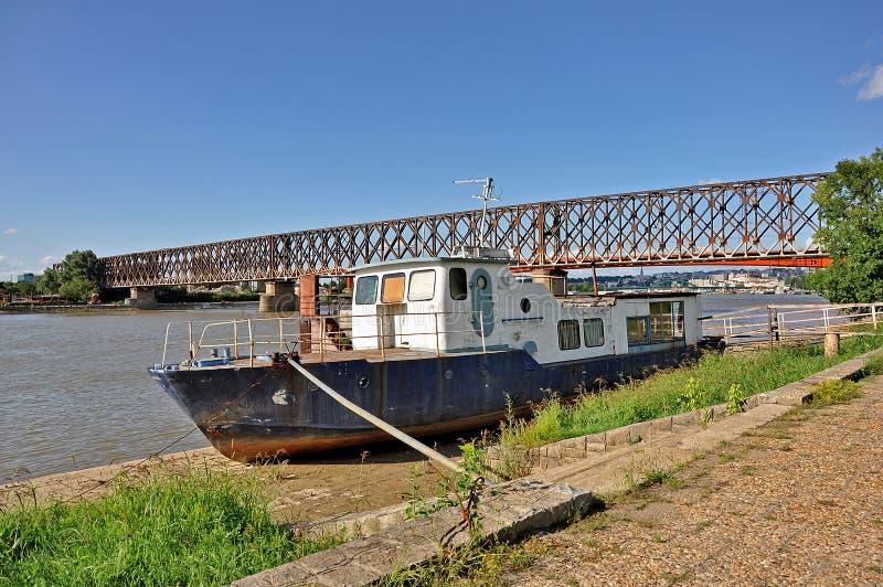 Gammal fiskebåt och bro bakom royaltyfria bilder