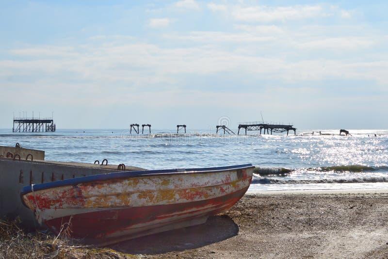 Gammal fiskebåt och förstörd oljeplattform royaltyfri foto