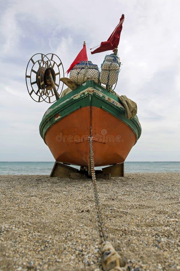 Gammal fiskebåt på den tomma stranden arkivfoto