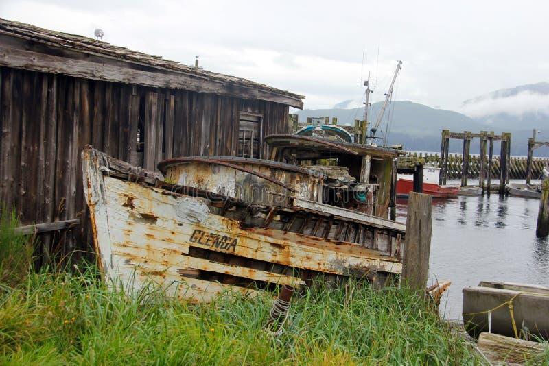 Gammal fiskebåt som är omgiven av land på den vakna fjärden, F. KR. arkivbild