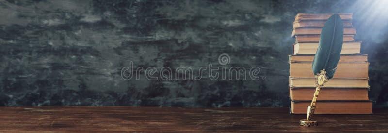 Gammal fj?dervingpennabl?ckpenna med bl?ckhornen och gamla b?cker ?ver tr?skrivbordet i framdel av svart v?ggbakgrund Gammal stil arkivbilder