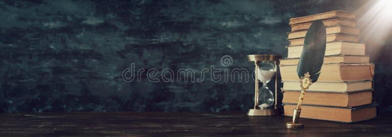 Gammal fj?dervingpennabl?ckpenna med bl?ckhornen och gamla b?cker ?ver tr?skrivbordet som ?r fr?mst av svart v?ggbakgrund Begrepp royaltyfria foton